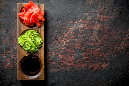 Wasabi, marinated ginger and soy sauce for Japanese sushi. On dark rustic background Stockfoto