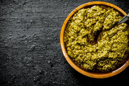 Pesto sauce in wooden bowl with spoon. On black rustic background