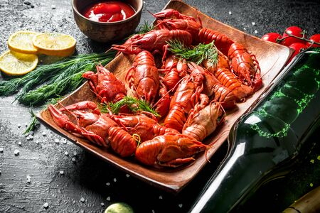 Delicious red boiled crayfish with a bottle of beer and tomato sauce. On black rustic background Stok Fotoğraf