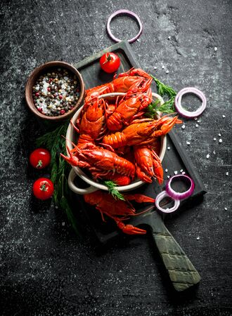 Boiled crayfish on a cutting Board with onion rings, tomatoes and spices. On dark rustic background