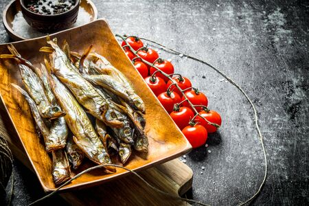 Smoked fish with tomatoes and spices. On dark rustic background Stok Fotoğraf