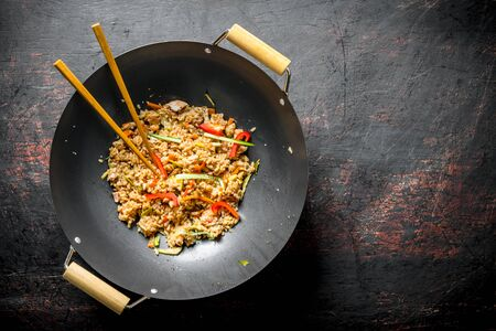 Chinese wok. Rice with vegetables and beef. On dark rustic background Stock Photo