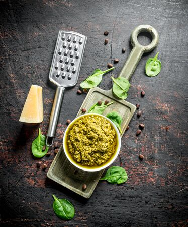 Pesto sauce on a cutting Board with Parmesan, pine nuts and Basil. On dark rustic background