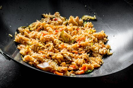 Chinese wok. Rice with beef and vegetables. On rustic background