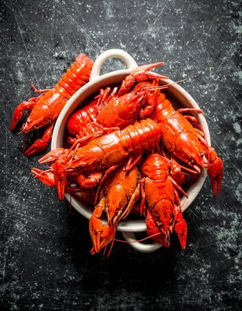 Red boiled crayfish in bowl. On dark rustic background Stok Fotoğraf