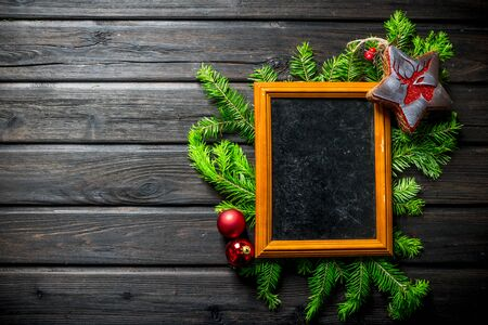 Empty Christmas photo frame with fir branches and decorations. On a dark wooden background Banque d'images - 132930173