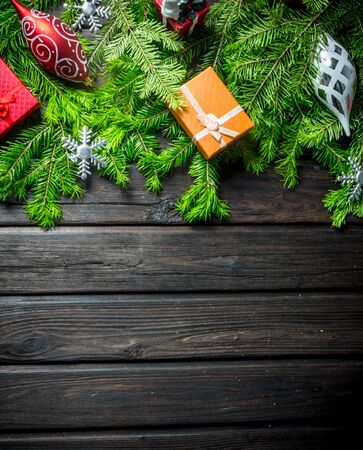 Christmas decorations and boxes on green fir branches. On a dark wooden background