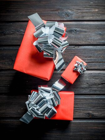 Red Christmas gift boxes with bows. On a dark wooden background