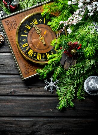 Retro clock with Christmas tree branches and decorations. On a dark wooden background Banque d'images - 132930561