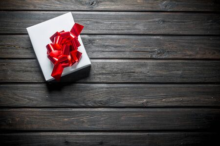 White Christmas box with red bow. On a dark wooden background Banque d'images - 132933784