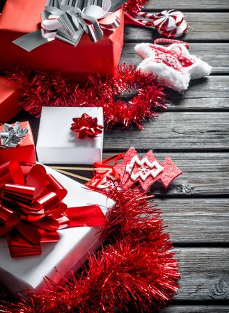 White and red Christmas gift boxes with decorations. On wooden background