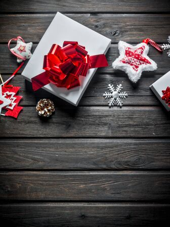 White Christmas gift boxes with Christmas decorations. On a dark wooden background Banque d'images - 132935866