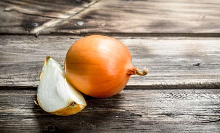 A piece and a head of onions. On wooden background