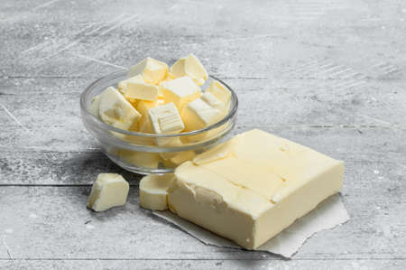 Butter in a glass bowl . On a rustic background.