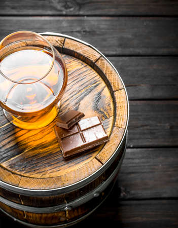 Cognac in a glass with chocolate on a barrel. On black wooden background