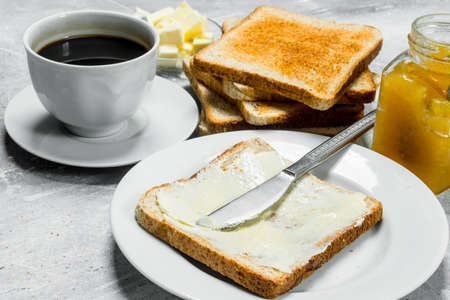 Toasted bread with butter and hot coffee. On a rustic background.