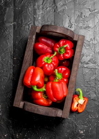 Ripe sweet pepper in the box. On black rustic background