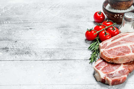 Raw pork steaks with tomatoes and hot chili peppers. On a rustic background.