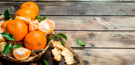 Juicy mandarins with leaves in basret. On wooden background