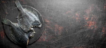 Raw fish flounder on a stone Board. On dark rustic background