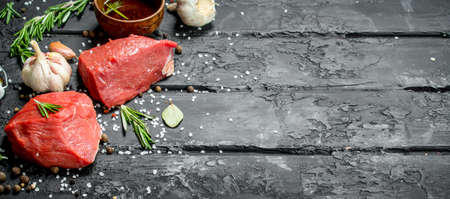 Raw meat. Sliced pieces of beef with spices and herbs on a wooden Board. On a black rustic background.