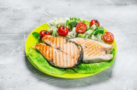 Grilled salmon steaks with broccoli and tomato salad. On a rustic background.