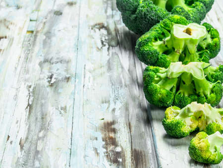 Lots of fresh broccoli. On a wooden background.