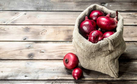 Fresh red onions in the sack. On wooden background