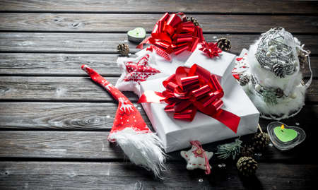 White gift boxes with bows, cones and candles. On wooden background