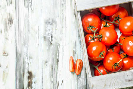 Fresh tomatoes in the box. On wooden background Reklamní fotografie