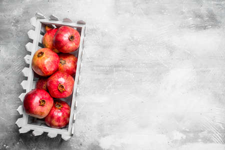 Red pomegranates in a plastic box. On rustic background