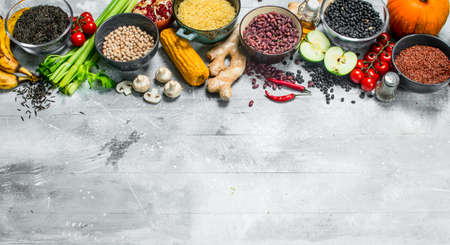 Organic food. Healthy assortment of vegetables and fruits with legumes. On a rustic background.