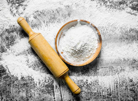 Flour background. Flour on a plate with a rolling pin. On rustic background
