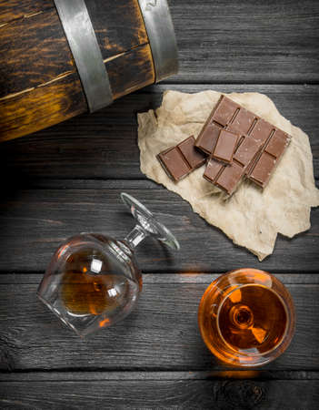 The cognac in the glass to the barrel and dark chocolate. On black wooden background