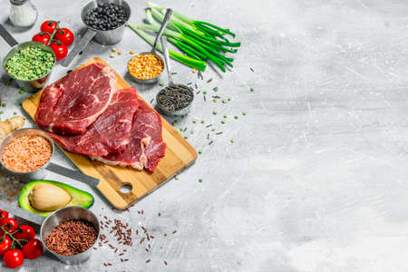 Healthy food. Raw beef meat with organic food. On a rustic background. Zdjęcie Seryjne