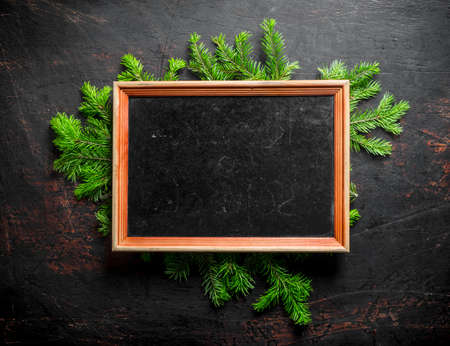 Empty Christmas photo frame with fir branches. On a dark rustic background 스톡 콘텐츠