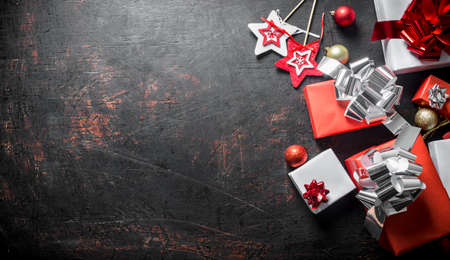 Different Christmas boxes and Christmas decorations. On a dark rustic background Zdjęcie Seryjne