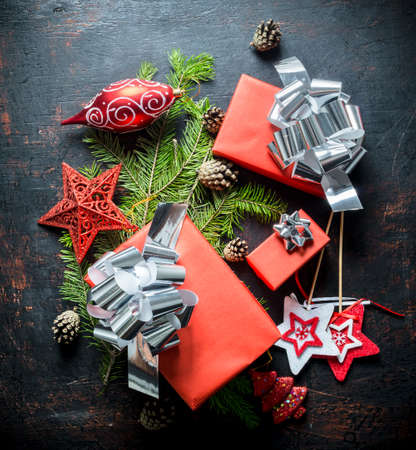 Gift boxes with Christmas decorations and fir branches. On a dark rustic background