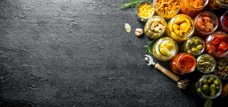 Assortment of various jars of preserved food. On black rustic background Stock Photo