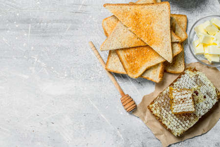 Breakfast. Toasted bread, honey with butter. On a rustic background