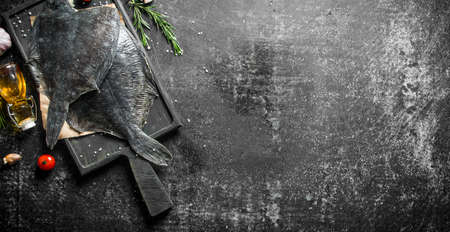 Fresh raw flounder on paper with rosemary. On dark rustic background