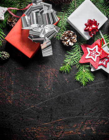 Christmas gift boxes with fir branches and cones. On a dark rustic background Zdjęcie Seryjne
