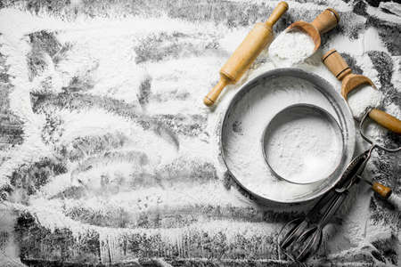 Flour with a sieve, scoops, rolling pin and mixer. On rustic background