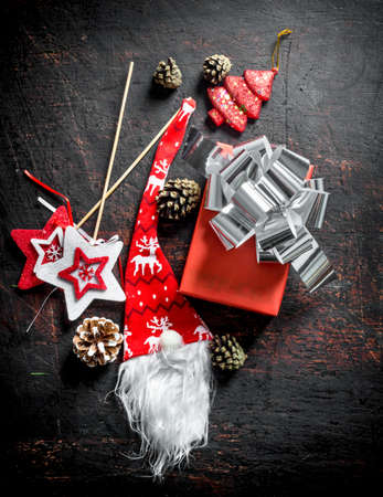 Red gift box with Christmas decorations and cones. On a dark rustic background Zdjęcie Seryjne