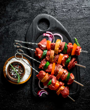 Raw kebab with vegetables, spices and onion slices. On black rustic background