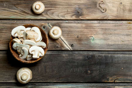 Pieces of fresh mushrooms in bowl. On wooden background