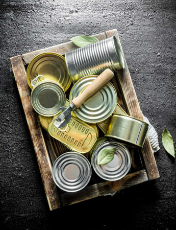 Assortment of closed tin cans with canned food on the tray. On black rustic background