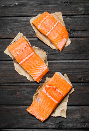 Raw salmon fish steaks on paper. On a wooden background.