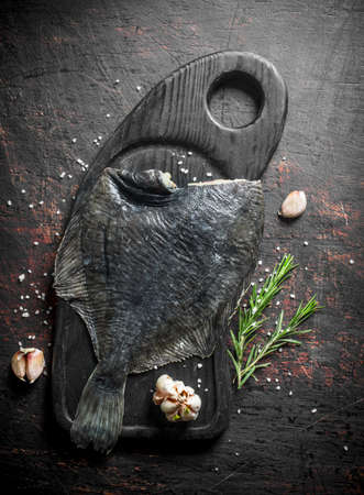 Fresh raw flounder with rosemary and garlic cloves. On dark rustic background