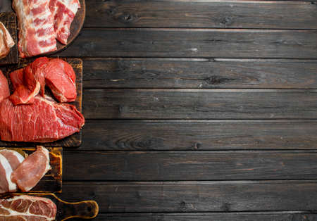 Raw meat. Different kinds of pork and beef meat. On a wooden background.
